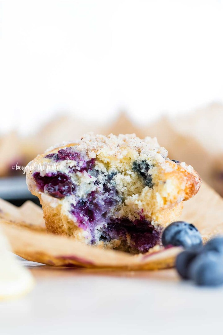 Image of unwrapped lemon blueberry streusel muffin with a bite taken out of it | All Images © Beyond the Butter™