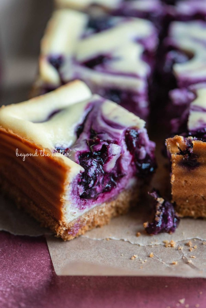 Slice of blueberry swirl cheesecake bar angled to see the side on parchment paper from BeyondtheButter.com | © Beyond the Butter®