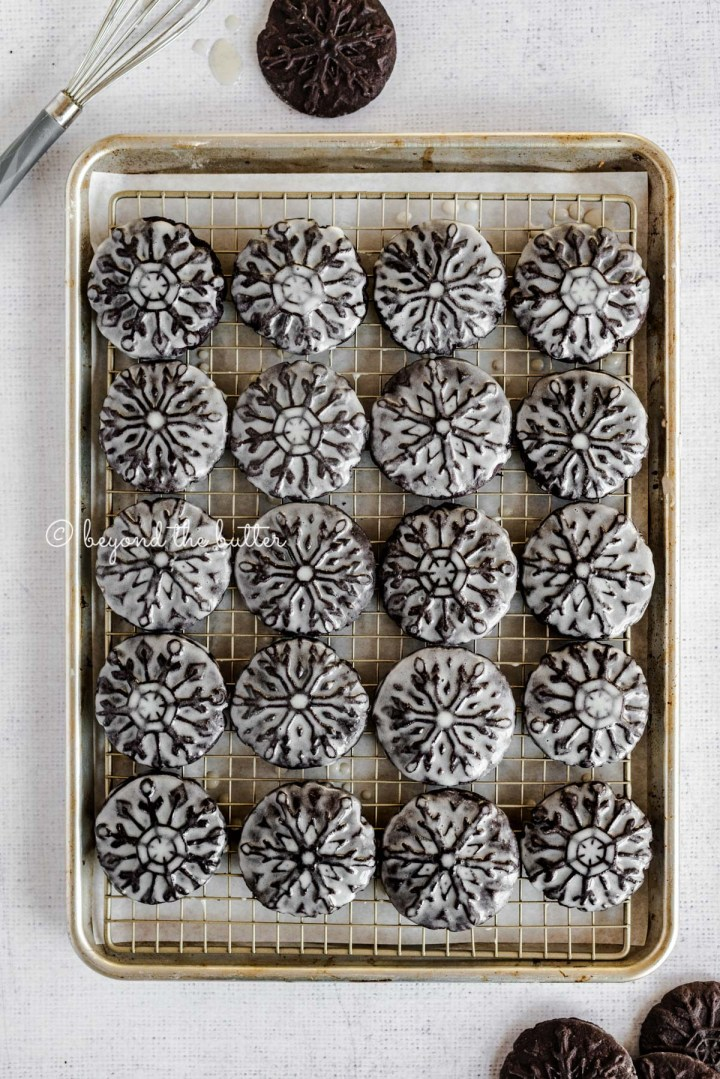 Overhead image of homemade oreo snowflake cookies on a baking sheet and wire cooling rack | All Images © Beyond the Butter®