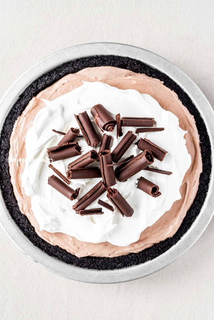 Overhead image of No-Bake Chocolate Cream Pie garnished with Cool Whip and chocolate curls | All Images © Beyond the Butter™
