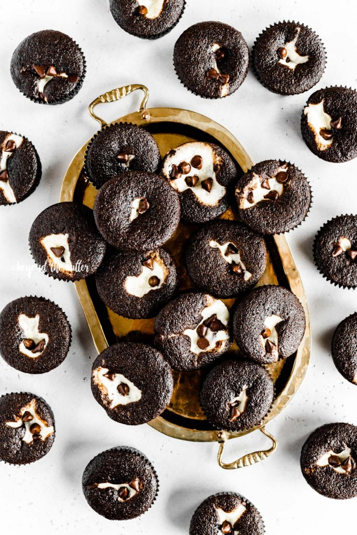 Overhead image of black bottom cupcakes randomly placed on gold serving plate on a gray background | All Images © Beyond the Butter™