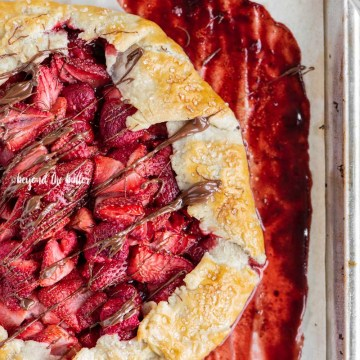 Overhead image of a Berry Nutella Galette on a baking sheet with Nutella drizzled over the top | All Images © Beyond the Butter™