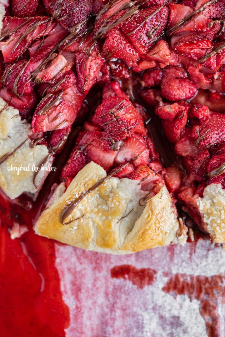 Overhead image of a slice of Berry Nutella Galette on a baking sheet with Nutella drizzled over the top | All Images © Beyond the Butter™