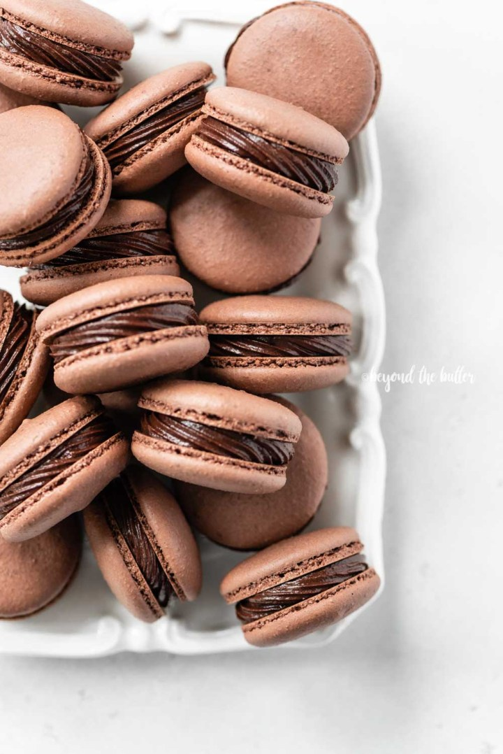 Overhead image of rectangular white plate full of chocolate macarons | All Images © Beyond the Butter™