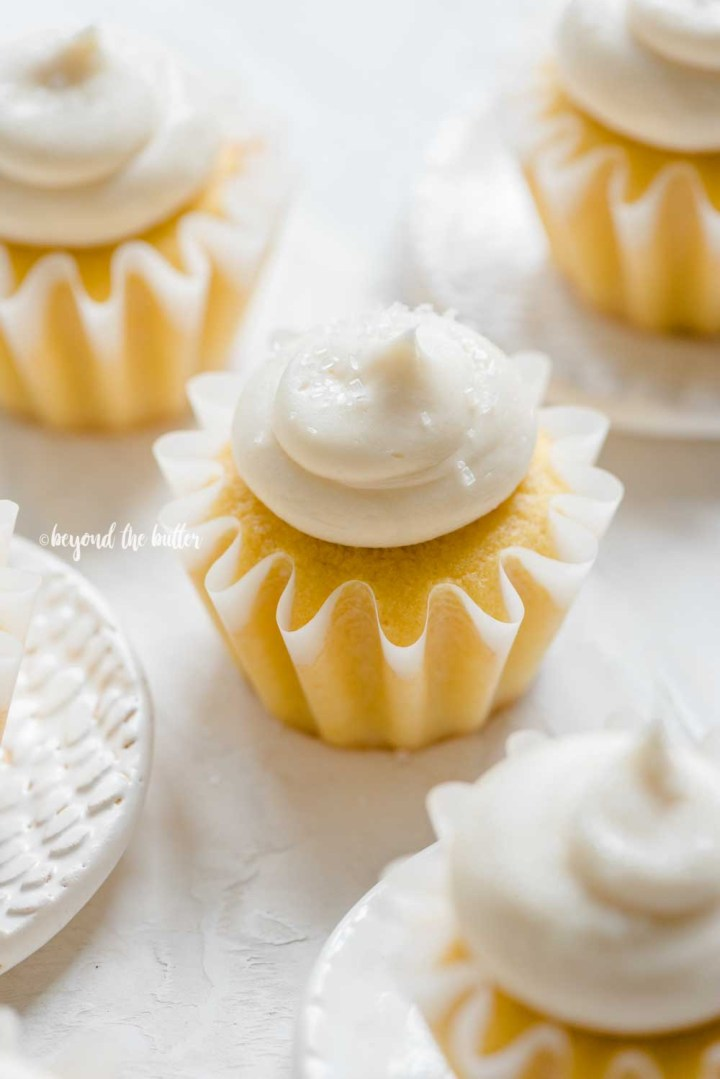 Angled image of vanilla cupcakes with small plate to the left side | All Images © Beyond the Butter™