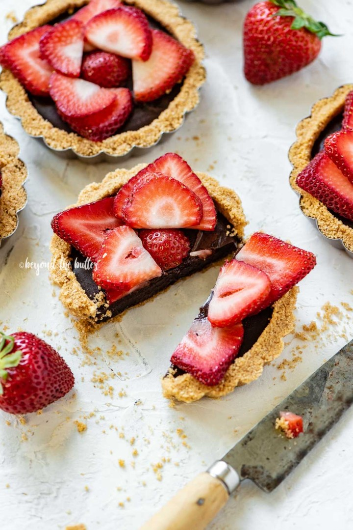 Angled image of mini strawberry nutella tarts on white stucco background with one sliced in half and opened | All Images © Beyond the Butter™