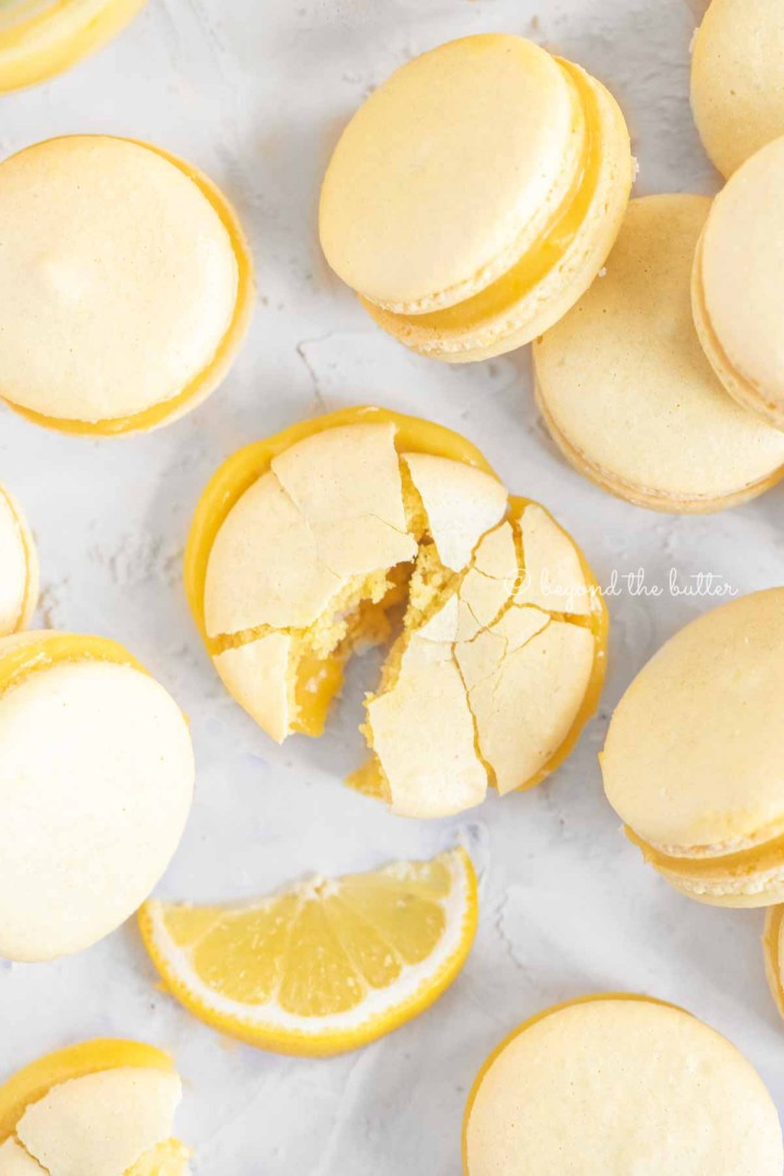 Overhead image randomly placed lemon macarons with the center macaron broken apart | All Images © Beyond the Butter™