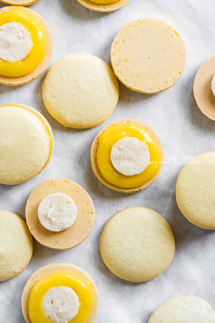 Overhead image of lemon bar macarons half opened topped with shortbread crust centers and lemon curd filling | All Images © Beyond the Butter™