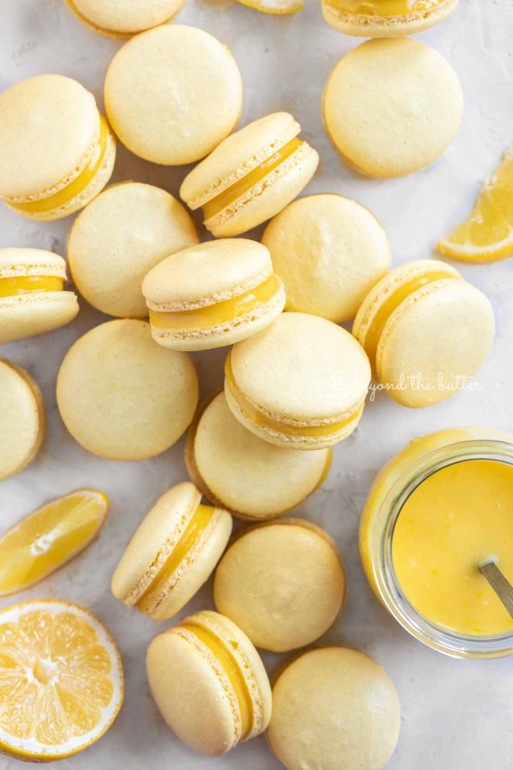 Overhead image of lemon bar macarons randomly placed around a small jar of lemon curd filling | All Images © Beyond the Butter™