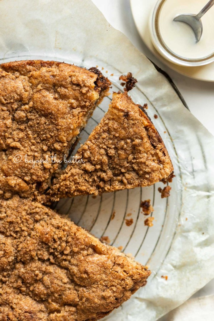 Apple coffee cake on a parchment paper lined wire cooling rack with slices removed and a simple vanilla glaze to the side | All Images © Beyond the Butter™