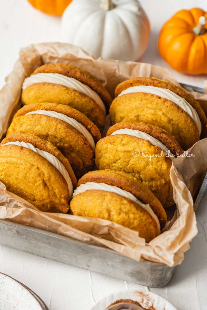 Angled image of pumpkin whoopie pies in parchment paper lined baking tin | All Images © Beyond the Butter™