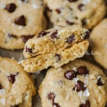 Salted chocolate chip shortbread cookies randomly placed on cookie sheet with the center cookie in half to show the middle | All Images © Beyond the Butter®