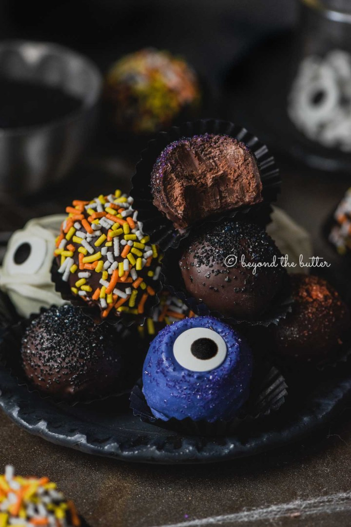 Plate of stacked homemade chocolate truffles with more around it on dark background | All Images © Beyond the Butter®