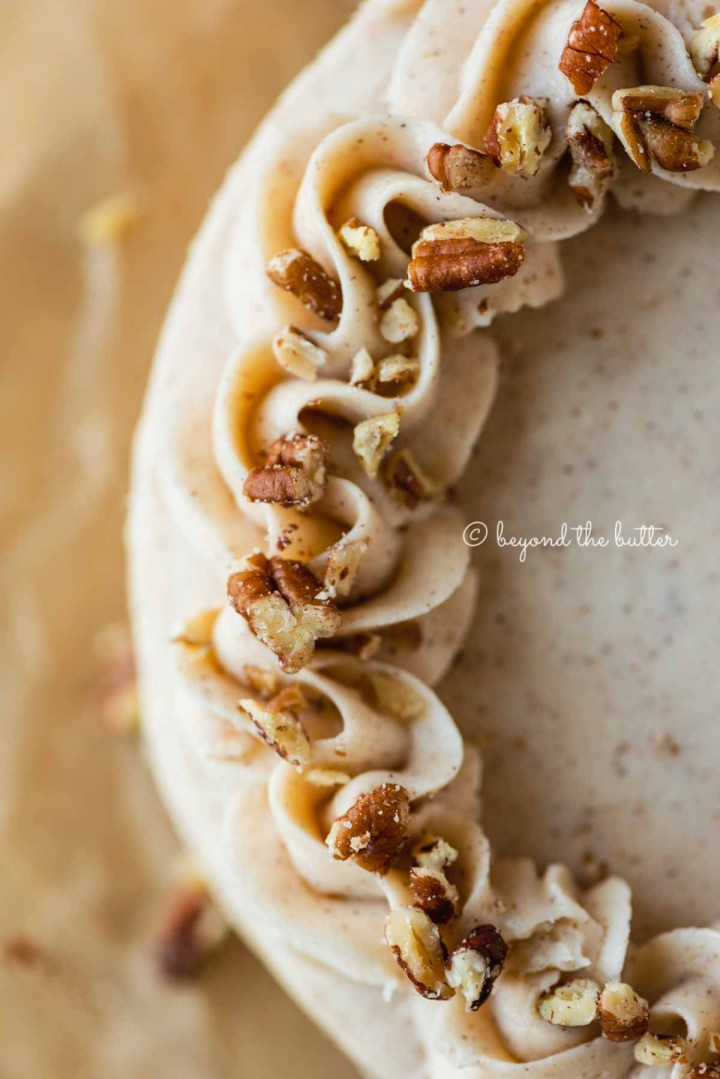 Detailed closeup image of frosted 6 inch carrot cake on sheets of brown parchment paper | All Images © Beyond the Butter®