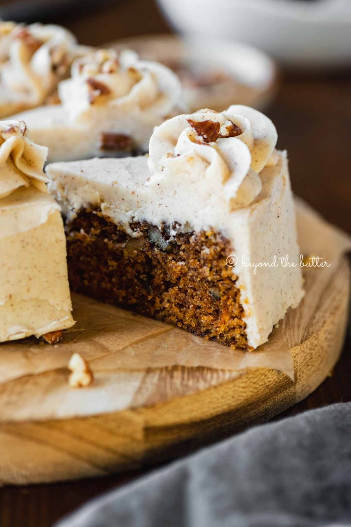 Angled closeup image of sliced 6 inch single layer carrot cake on parchment paper | All Images © Beyond the Butter®