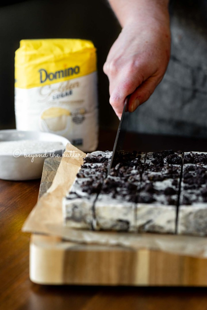 Cutting the cookies and cream fudge with small bag of Domino® Golden Sugar in the background | All Images © Beyond the Butter®