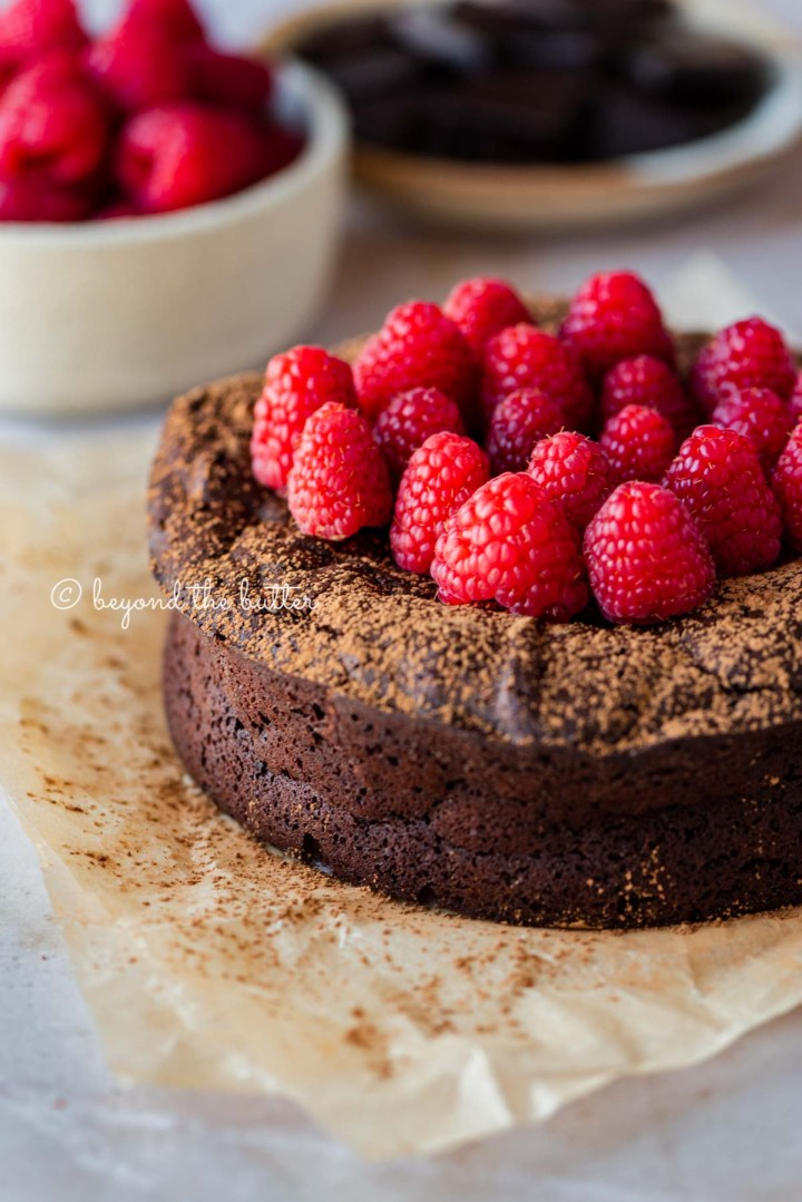 Small flourless chocolate cake topped with cocoa powder and fresh raspberries on parchment paper | All images © Beyond the Butter®