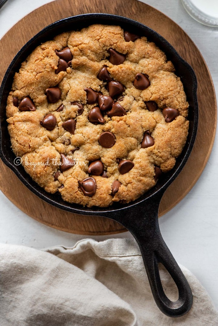 Just baked chocolate chip skillet cookies on light gray background with cloth napkin | All Images © Beyond the Butter®