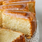 Sliced lemon cream cheese pound cake with a lemon glaze on a cake stand | © Beyond the Butter®