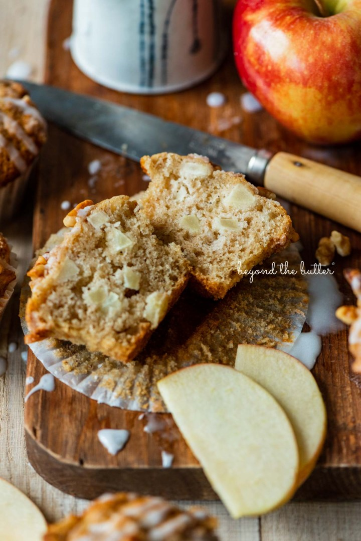 Sliced apple cinnamon streusel muffin on a wood cutting board with sliced apples | © Beyond the Butter®