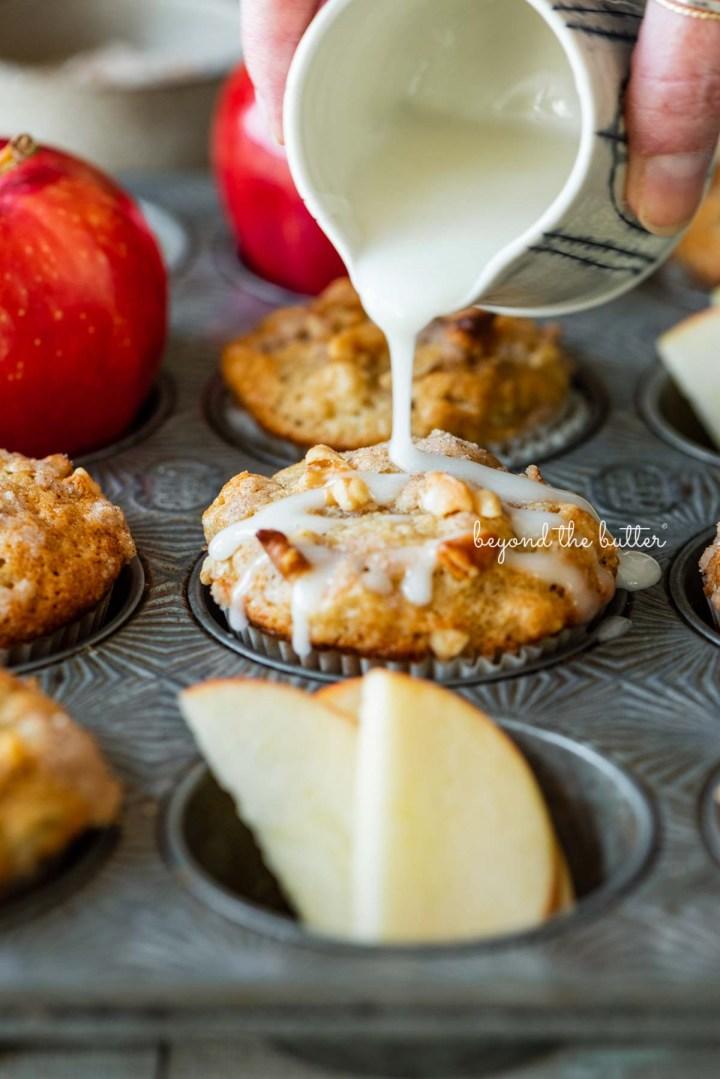 Drizzling warm vanilla glaze over top of apple cinnamon struesel muffins | © Beyond the Butter®