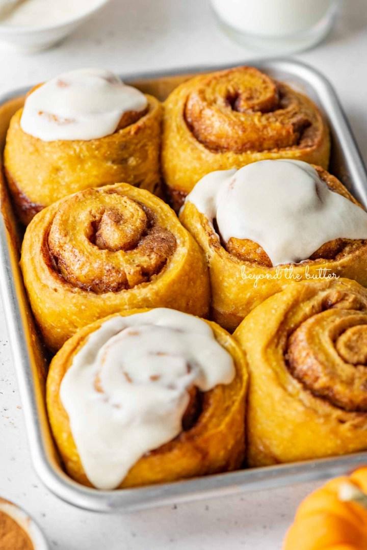 Small baking sheet of half frosted pumpkin cinnamon rolls | © Beyond the Butter®