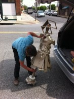 "Mackenzie Holland coaxing her sculpture, appropriately titled ""What is Happening?"" out of the truck"
