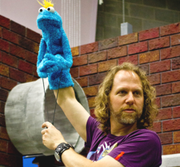 Peter Linz works with a blue puppet with yellow hair