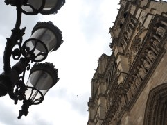 Lacy ironwork crowning the street lamps is overshadowed by towering layers of carved stone