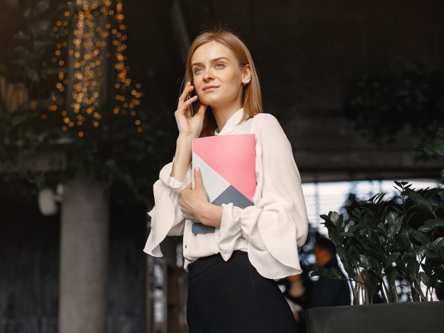 businesswoman-with-notebook-calling-on-smartphone-in-cafe-4173265