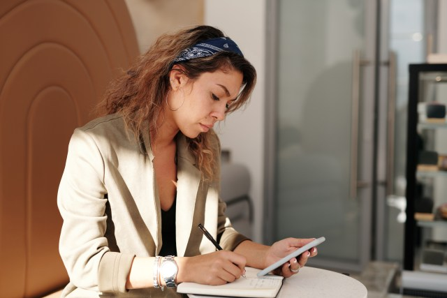 woman-holding-smartphone-writing-on-notebook-4063862