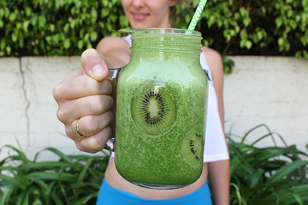 Woman holding green Shakeology shake