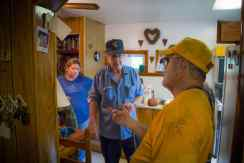 A disaster response volunteer explains the cleanup process to homeowners in West Virginia.