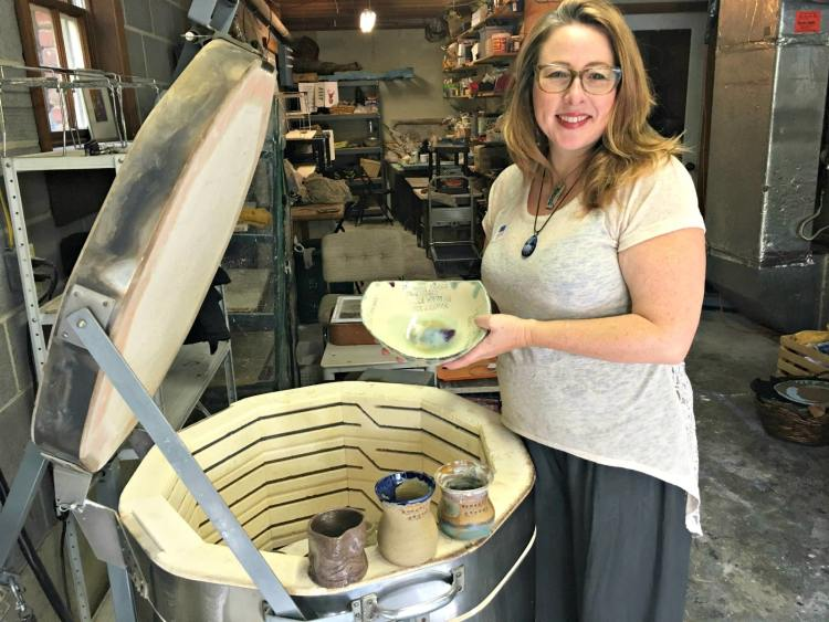 One of the Roebuck Springs potters, Nichole Lariscy Moore, with finished work near her kiln.
