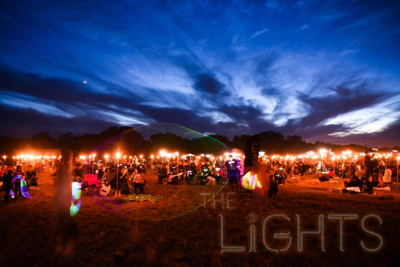 Tiki torches light the grounds as festival goers wait for nightfall. (Photo via The Lights Fest)