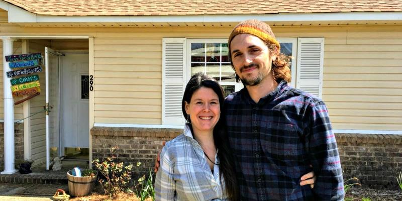 Joanna and Travor Mann in front of their home.