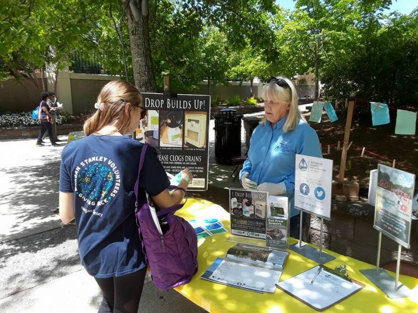 Photo shows one woman talking to another women at a booth on Earth Day at Birmingham Botanical Gardens in Alabama. The topic of the booth is about how oil builds up in drains and clogs them.