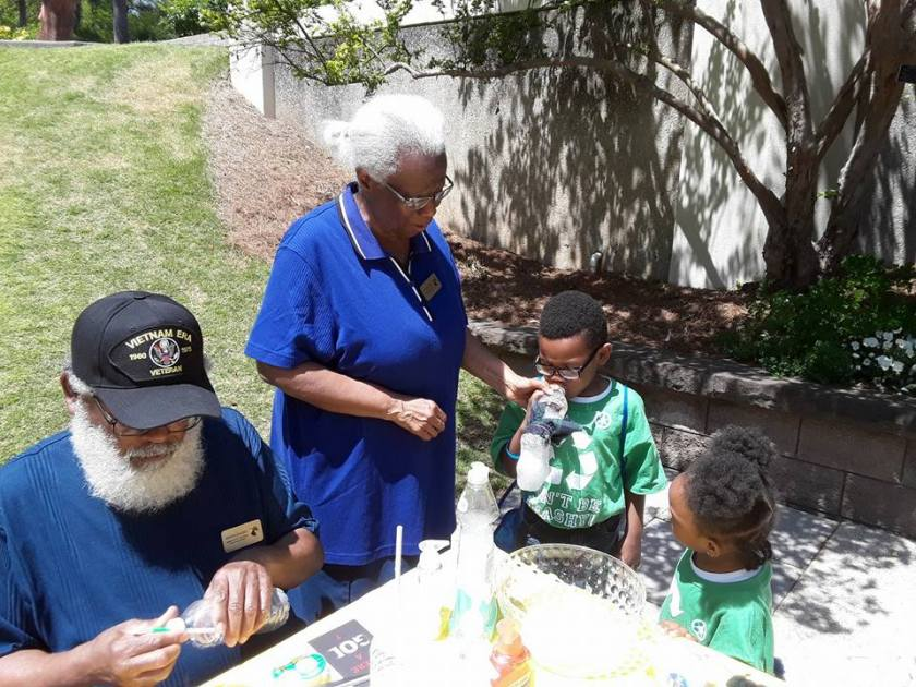Photo shows the Burks wearing blue shirts leading an environmental science lesson with two small children wearing green shirts on Earth Day at Birmingham Botanical Gardens in Alabama