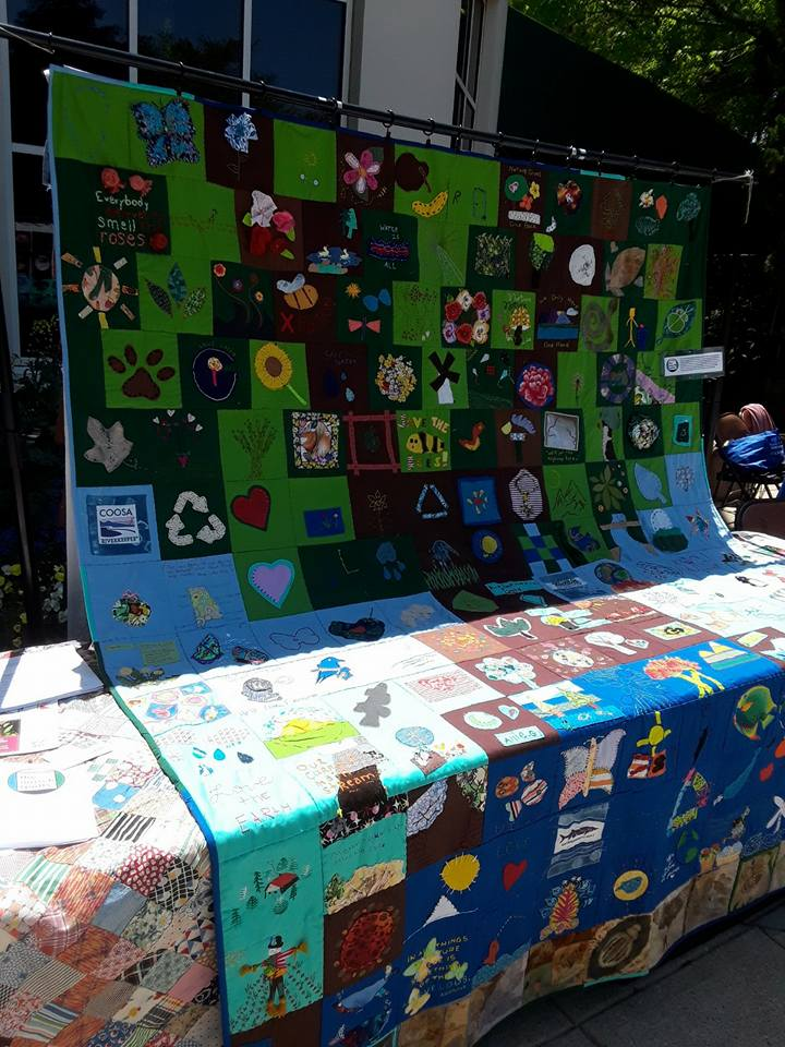 Photo shows a quilt-covered table. A large community quilt created from felt squares by Earth Day attendees at Birmingham Botanical Gardens hangs above it.