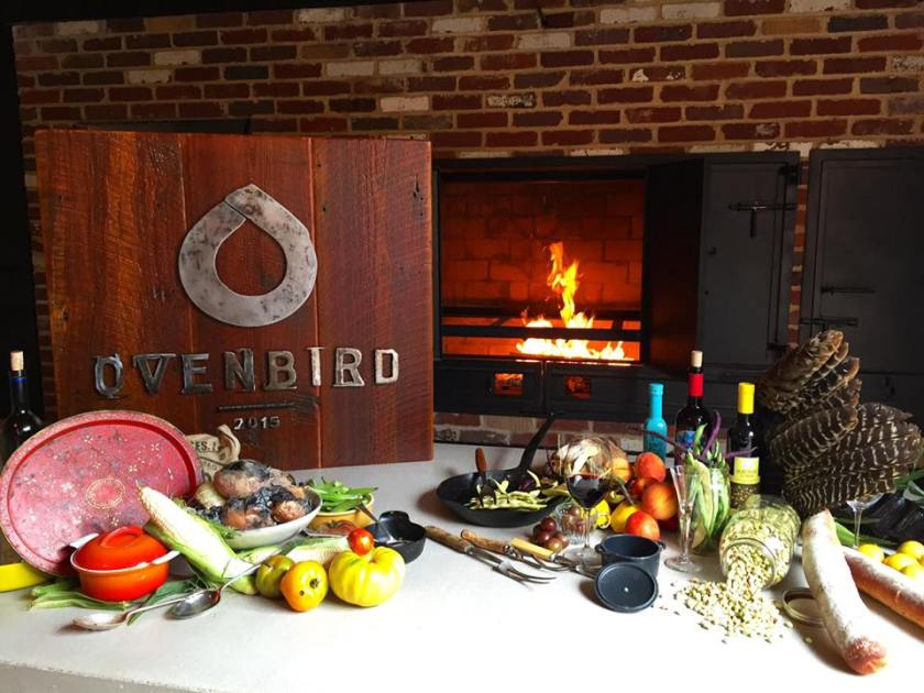 Photo shows a brick hearth with fire, a table full of fresh produce and an wooden plaque bearing the logo for OvenBird, a restaurant based in the Pepper Place district in Birmingham, Alabama