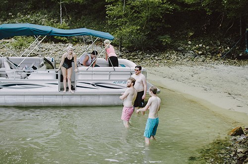 Group of friends wade on the shoreline of Smith Lake