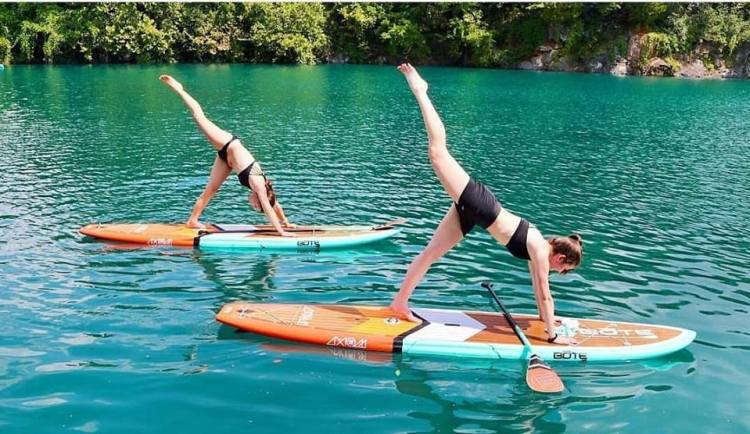 Two women doing paddle board yoga