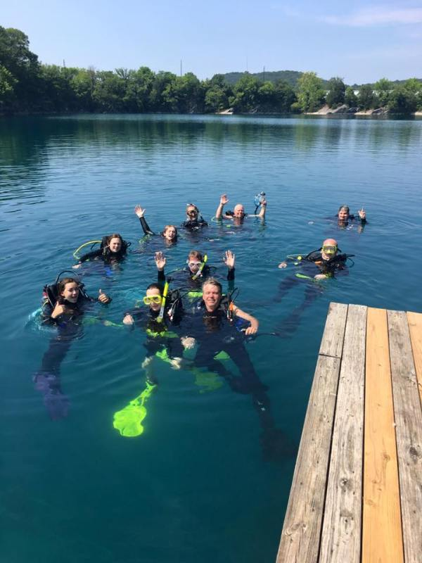 Scuba divers float on surface of lake