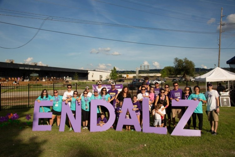 Participant of the Walk to End Alzheimer's hold up END ALZ sign at Sloss Furnaces in Birmingham, Alabama