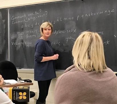 Lady writing on chalkboard looking at students in class at Samford Academy of the Arts