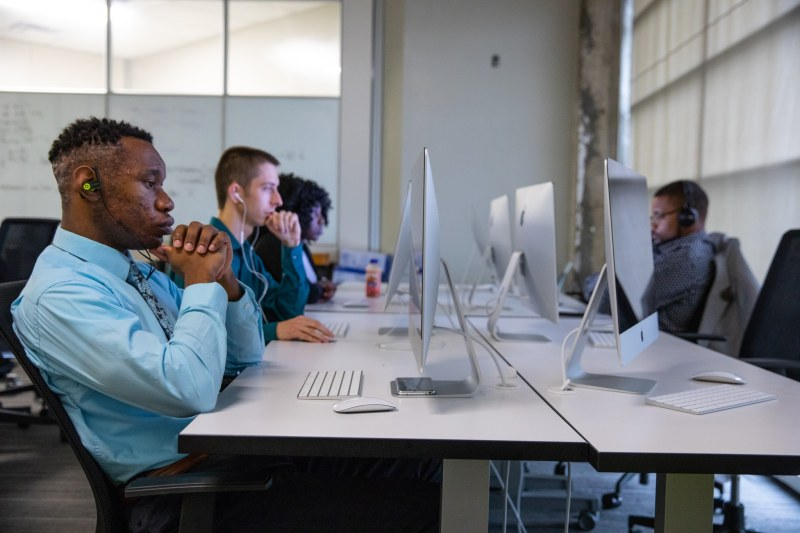 A table full of tech students working at their computers at Innovate Birmingham's lab.