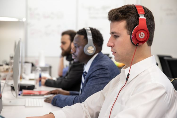 Three male students look at their computers with headphones on.