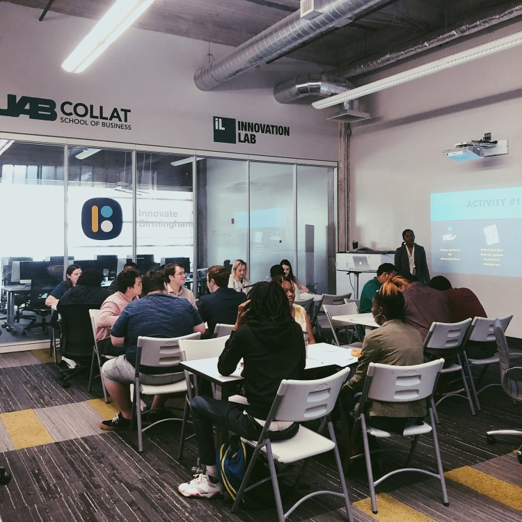 A classroom full of students in Innovate Birmingham's Innovation Lab. They are observing a presentation.