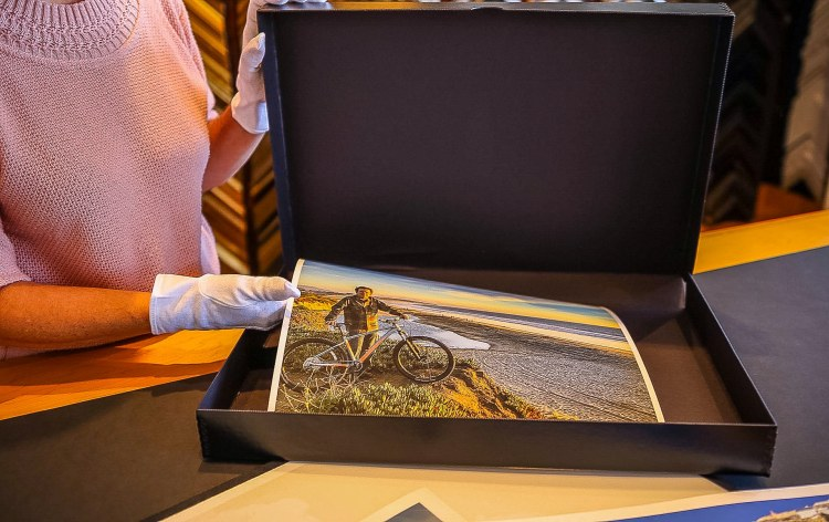 Carla is wearing white cotton gloves to handle a large archival photo while placing it in an acid-free storage container.