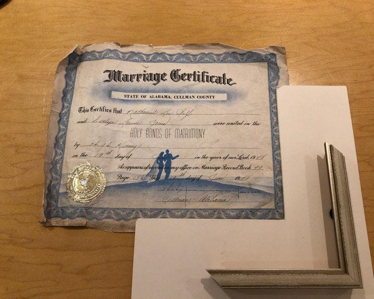 A wedding certificate before the restoration. It is surrounded by the frame and mat sample.